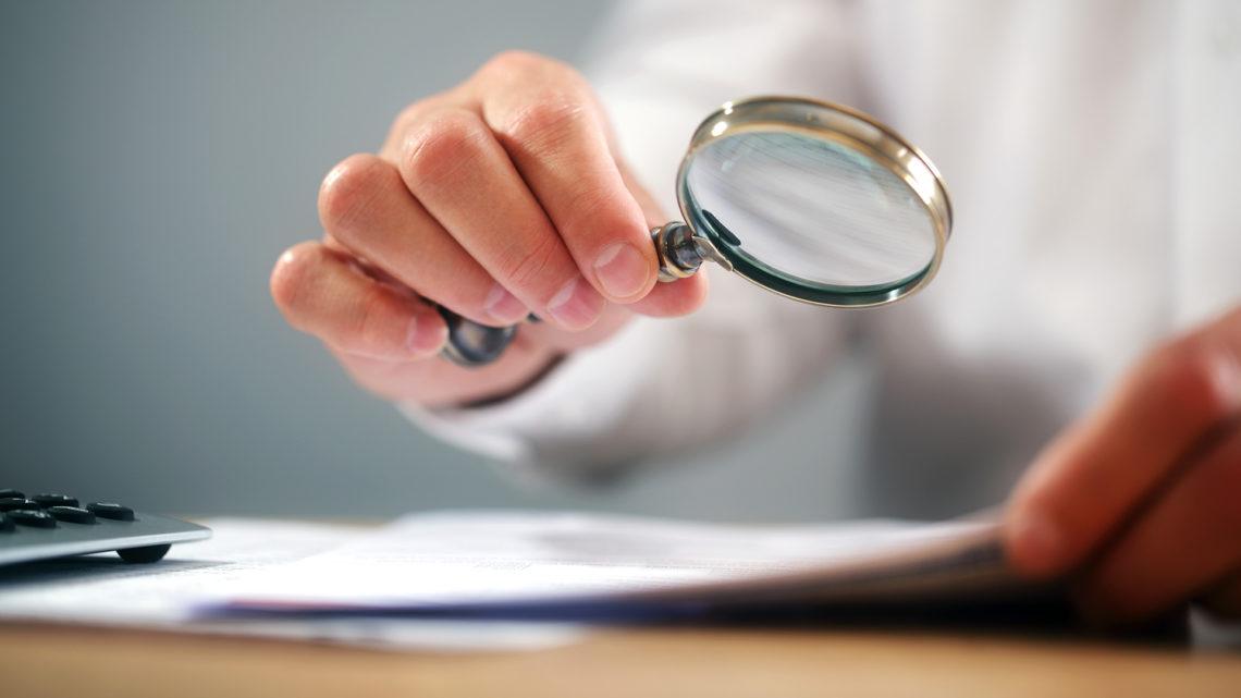 Foto de homem usando lupa para analisar documentos