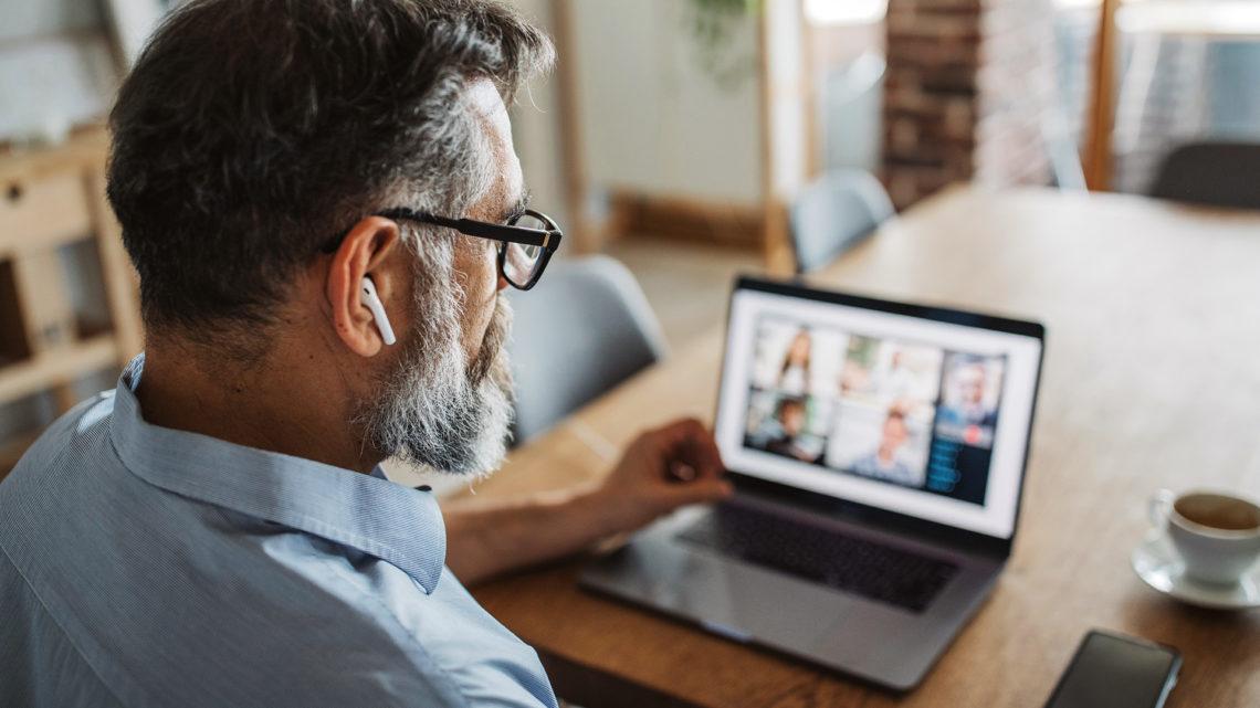 Foto de um homem fazendo uma reunião virtual com outras pessoas