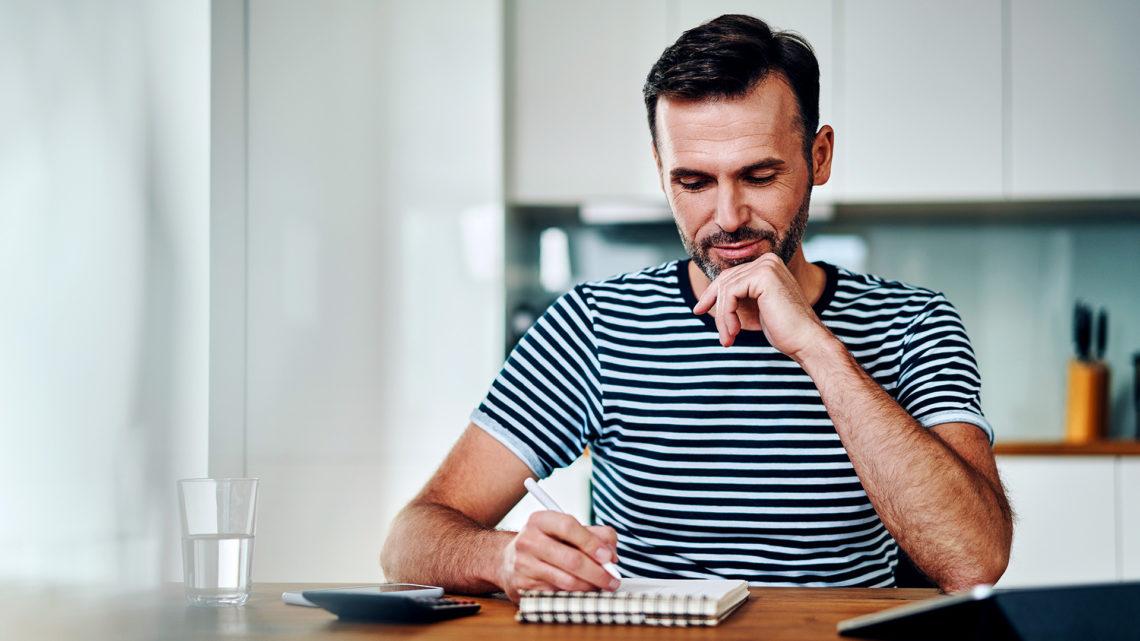 Foto de homem pensativo escrevendo no caderno com calculadora do lado