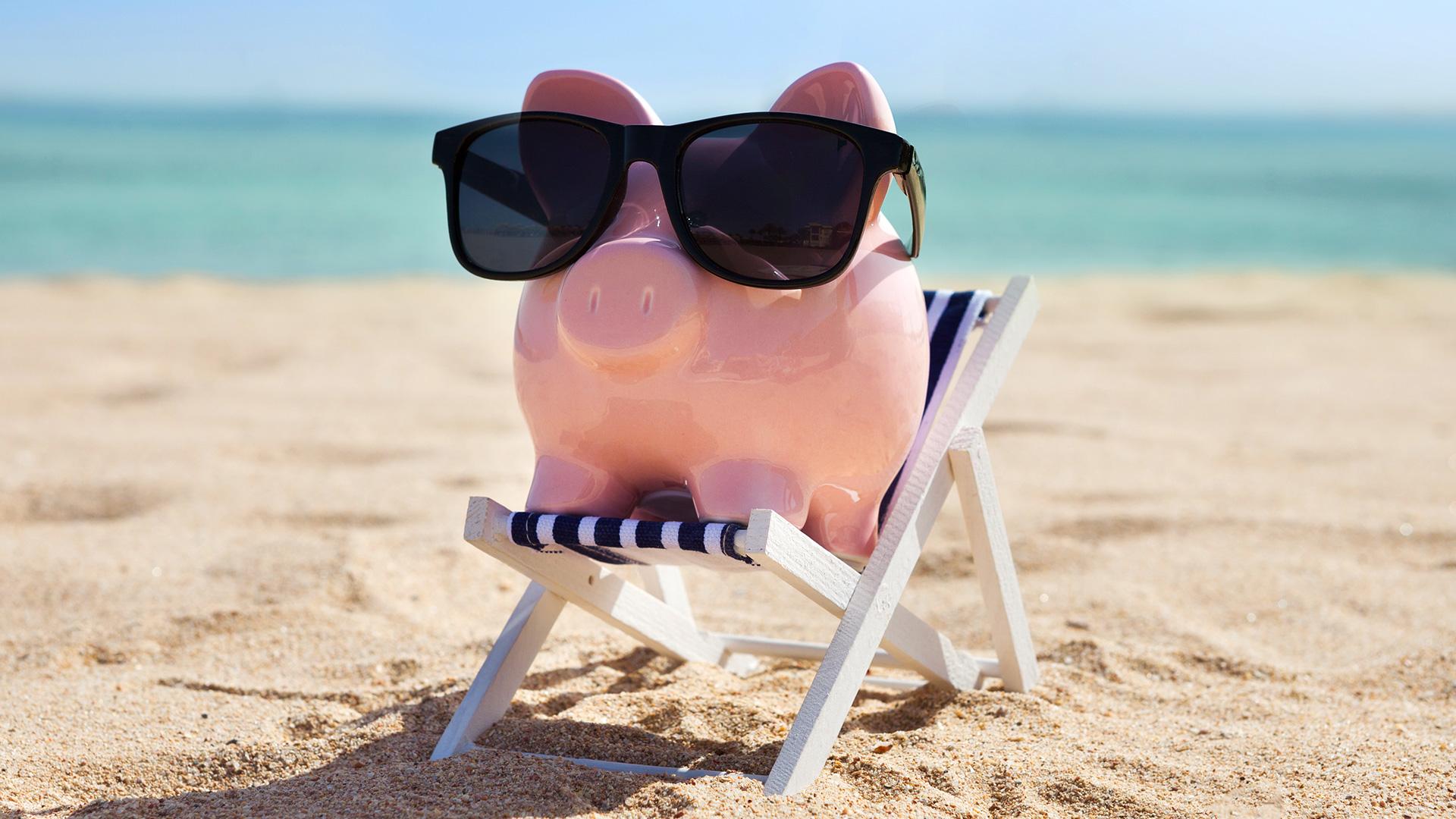 Foto de um cofre de porquinho usando óculos de sol na praia