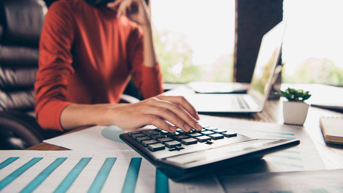 Foto de uma mulher usando uma calculadora, com documentos e notebook na mesa.