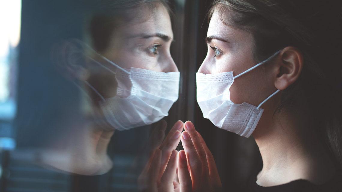 Foto de mulher usando máscara olhando seu reflexo na janela.