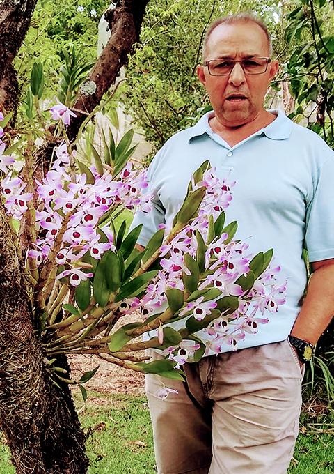 Foto do aposentado José Geraldo de Oliveira, que usa óculos e camisa polo azul e está junto à flores.