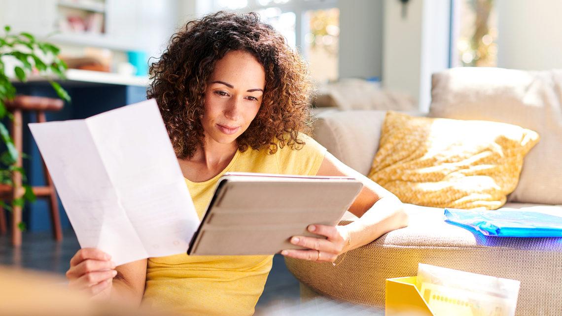 Foto de uma mulher olhando um tablet e segurando um papel na mão.